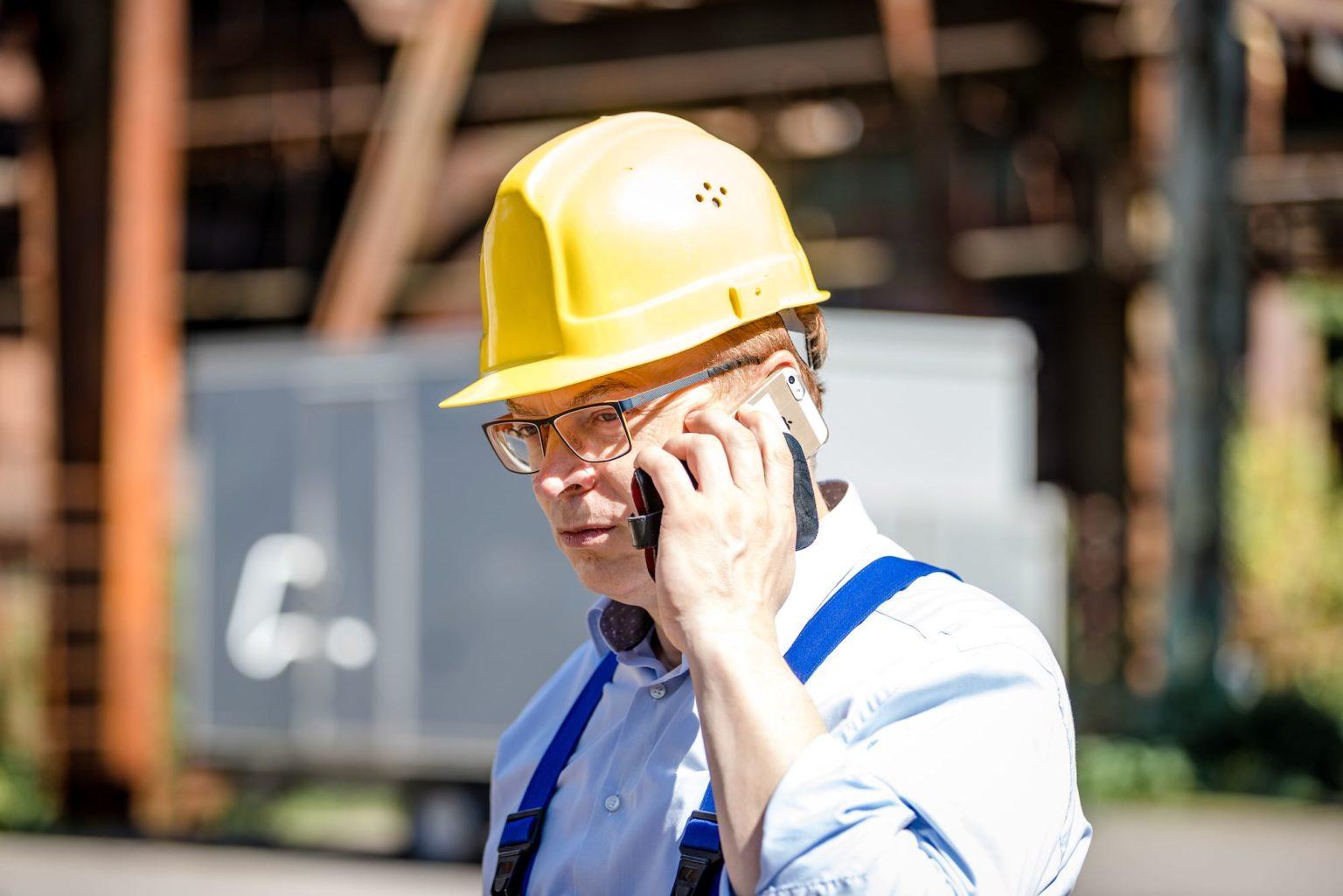 Wolfgang Schmid am Handy im Stahlwerk